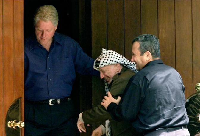 REUTERS PICTURES OF THE DECADE.  Israeli Prime Minister Ehud Barak (R) jokingly pushes Palestinian President Yasser Arafat (C) into the Laurel cabin on the grounds of Camp David as U.S. President Bill Clinton watches during peace talks, July 11, 2000. Arafat and Barak were insisting that the other proceed through the door first. Camp David is the venue where Egypt and Israel made peace in September 1978, and the Laurel cabin was the site of many of the meetings. REUTERS/Win McNamee (UNITED STATES)