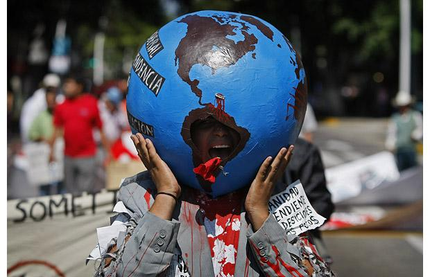 An anti-globalisation demonstrator shouts slogans during a march against the North American Leaders summit in Guadalajara Picture: AP