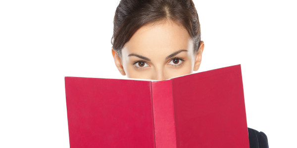 Close-up portrait of female in business suit peeking over the book, isolated on white background