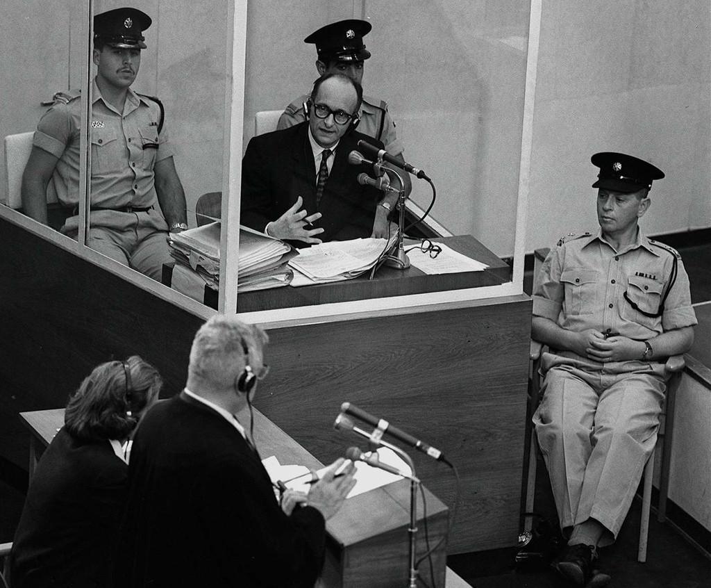"""אדולף אייכמן בתא הזכוכית בעת משפטו בירושלים, 1961. מקור: לשכת העיתונות הממשלתית (לע""""מ)."""