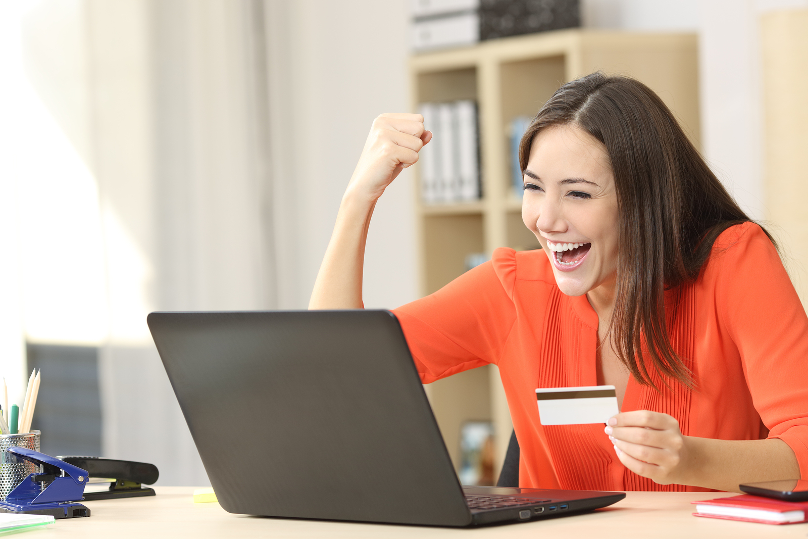 Euphoric shopper buying on line with a laptop and a credit card at home or office bigstock-131212394-2