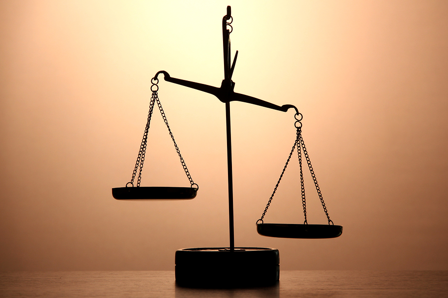 Gold scales of justice on brown background bigstock- 40560358