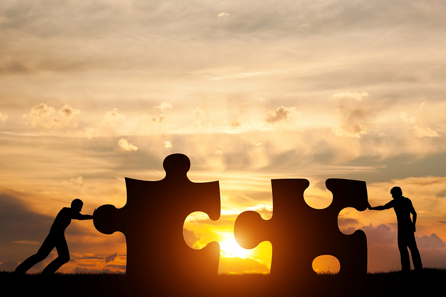 Bigstock-127357196 Two men connect two puzzle pieces. Sunset sky. Concept of business solution, teamwork, solving a problem challenge